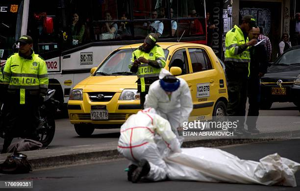 Forensic personnel work on the scene of a motorcycle accident in which a woman was killed in Bogota on August 17 2013 According to Bogota's Secretary...