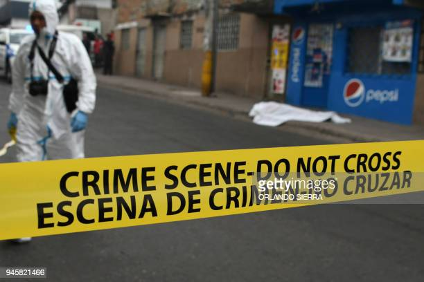 Forensic personnel work on the scene where a student from Vicente Caceres Central Institute was shot dead by alleged gang members when she was...