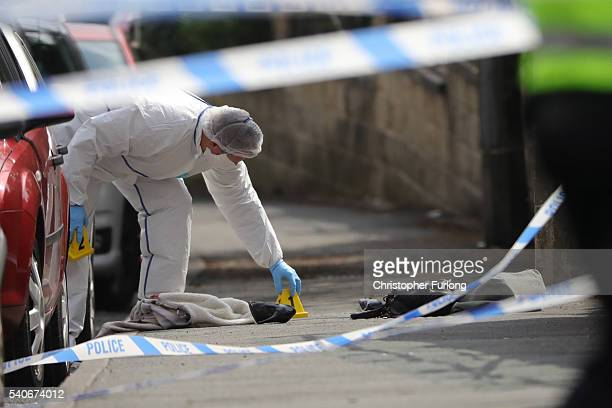Forensic police examine shoes and a handbag at the scene after Jo Cox Labour MP for Batley and Spen was shot and stabbed by an attacker at her...