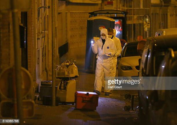 Forensic police investigate outside the building where raids took place in which several people, including Paris attacks suspect Salah Abdeslam, were...