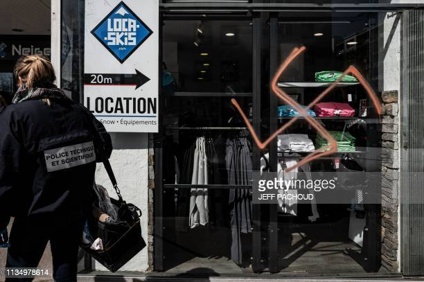 A forensic police officer investigates a swastika spray painted on a shop's window in Lyon on April 5 2019 Around twenty antiSemitic and racist...