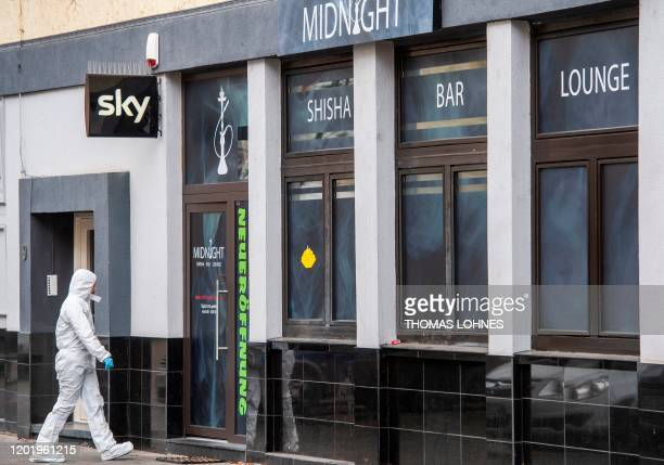 A forensic police officer is pictured at a crime scene in front of a bar at the Heumarkt in the centre of Hanau near Frankfurt am Main western...