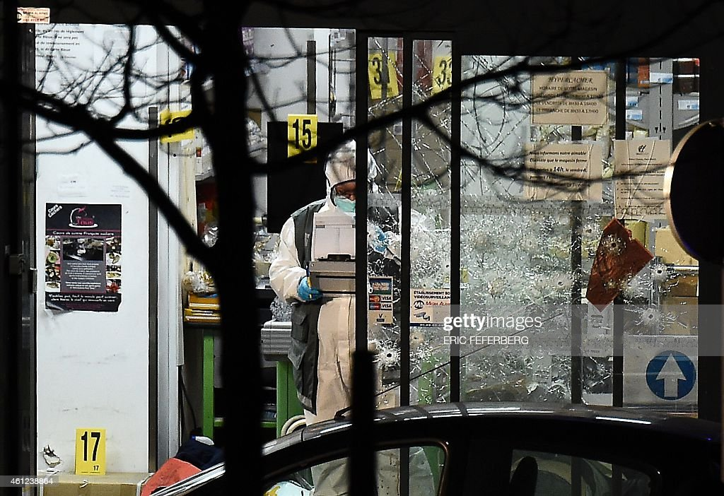 A forensic police officer works next to the bullet-riddled windows of the Hyper Cacher kosher grocery store near Porte de Vincennes in eastern Paris on January 9, 2015 after police launched an assault killing the gunman holed up in the market and freeing the hostages. The gunman killed by police after taking hostages at a Jewish supermarket in Paris told BFMTV station he had 'co-ordinated' with the suspected Charlie Hebdo attackers and belonged to the Islamic State group.