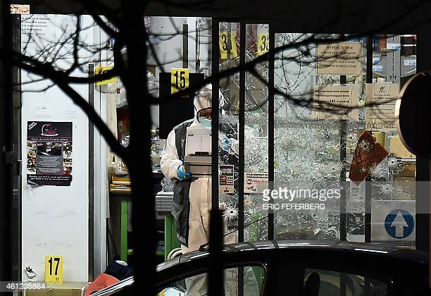 A forensic police officer works next to the bulletriddled windows of the Hyper Cacher kosher grocery store near Porte de Vincennes in eastern Paris...
