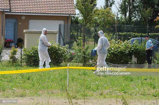 Forensic police officers examine the garden outside a house where the bodies of a woman and two girls were found and a man and a young boy were found...