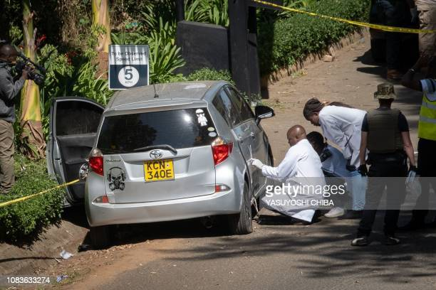 Forensic police officers investigate an abandoned car alledged to have been used by attackers, at the entrance of a luxury hotel complex attacked by...
