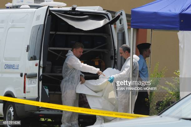 Forensic police officers investigate around a house where the bodies of a woman and two girls were found and a man and a young boy were found...