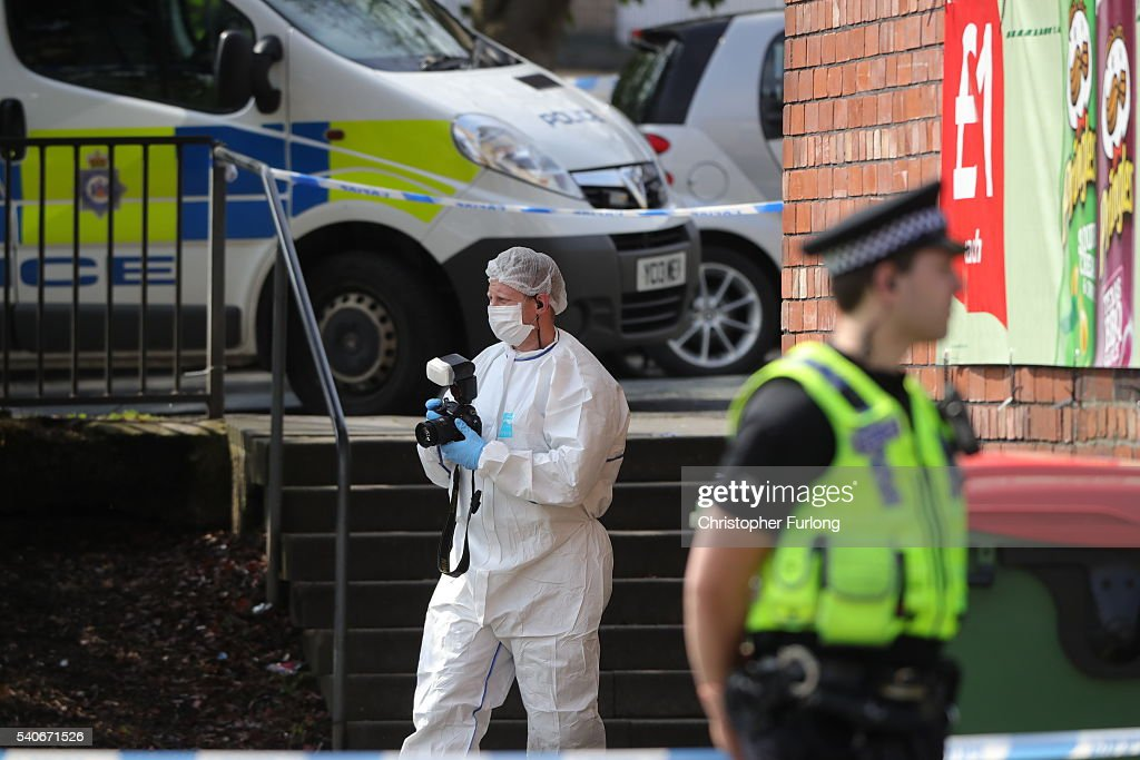 Forensic police take photos at the scene after Jo Cox Labour