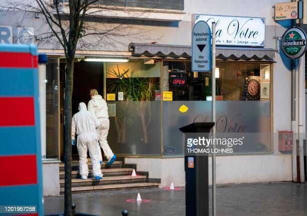 Forensic police work at a crime scene in front of a bar at the Heumarkt in the centre of Hanau near Frankfurt am Main western Germany on February 20...