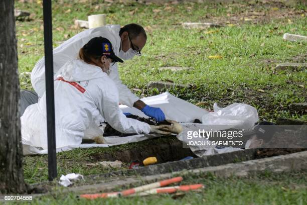 Forensic science technicians exhume bodies at the Universal Cemetery in Medellin Colombia on June 5 2017 The Attorney General's Office reported that...