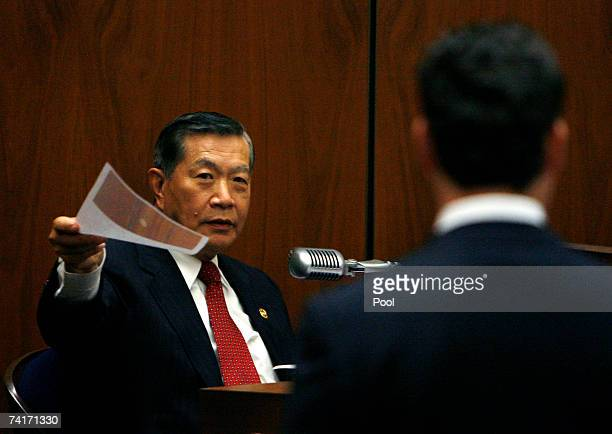 Forensic scientist Dr Henry C Lee reviews photographs of evidence as prosecutor Alan Jackson waits during the Phil Spector murder trial at Los...