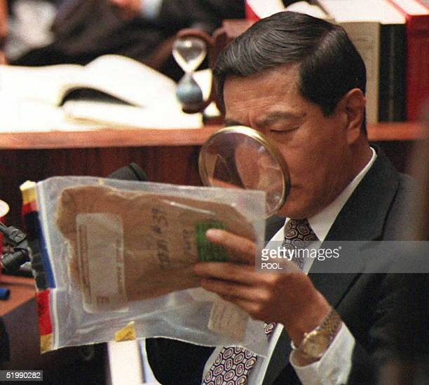 Forensic scientist Dr Henry Lee uses a magnifying glass to look at blood stains on an envelope used to collect the eyeglasses found at the Bundy...