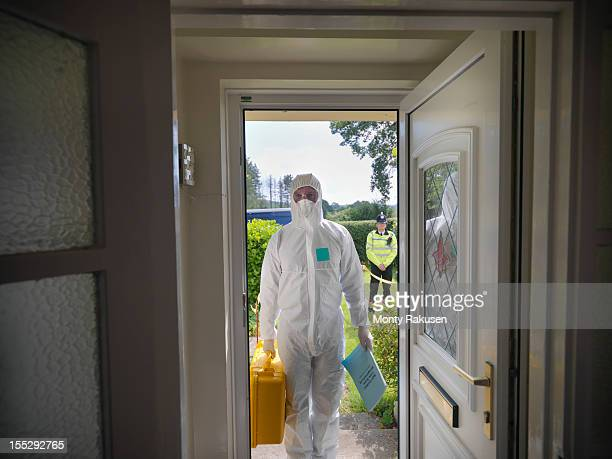 forensic scientist entering house at crime scene, policeman in background - protective suit stock pictures, royalty-free photos & images