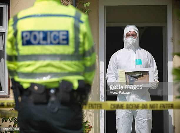 Forensic scientist holding evidence box containing firearm at crime scene, policeman in foreground