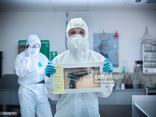 forensic scientist holding evidence box containing gun from crime scene - forense fotografías e imágenes de stock