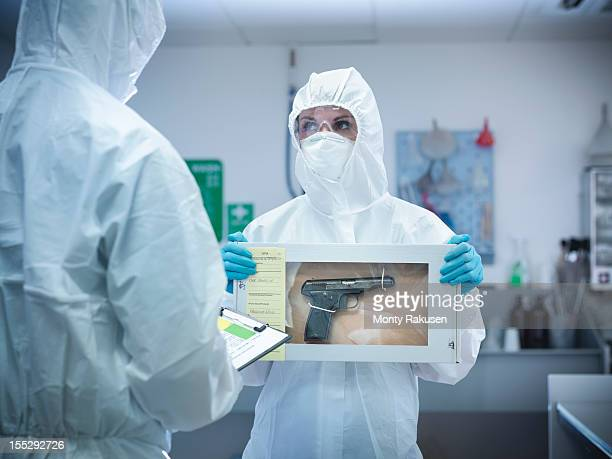 Forensic scientist holding evidence box containing gun from crime scene