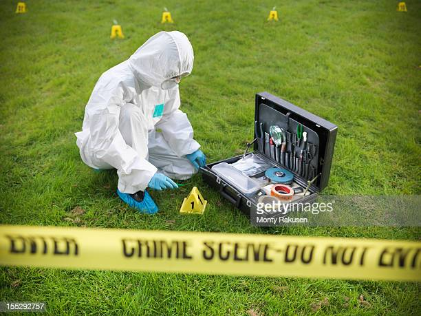 forensic scientist inspecting toolkit at crime scene, police tape in foreground - tatort von menschen geschaffener raum stock-fotos und bilder