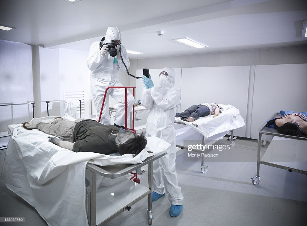 Forensic scientist photographing artificial body in mortuary at training facility : Stock Photo