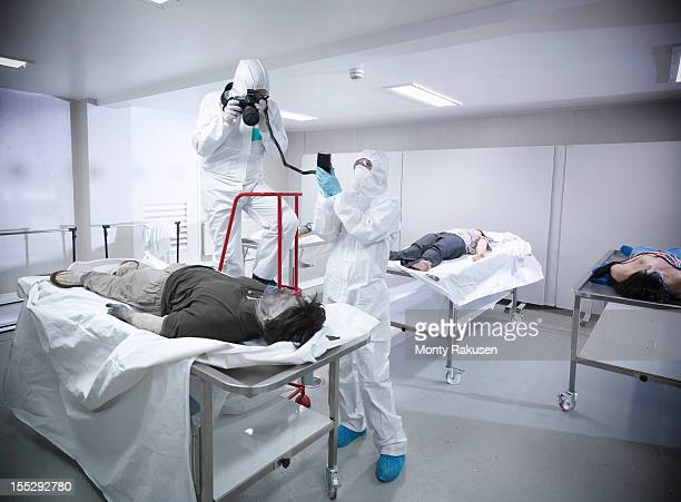 Forensic scientist photographing artificial body in mortuary at training facility