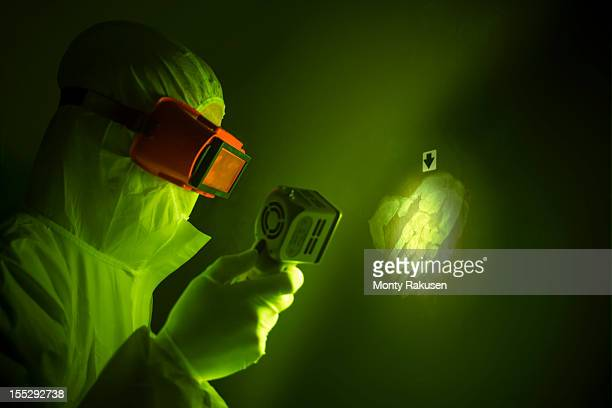 forensic scientist using finger print light to find hand print on wall at crime scene - forense fotografías e imágenes de stock
