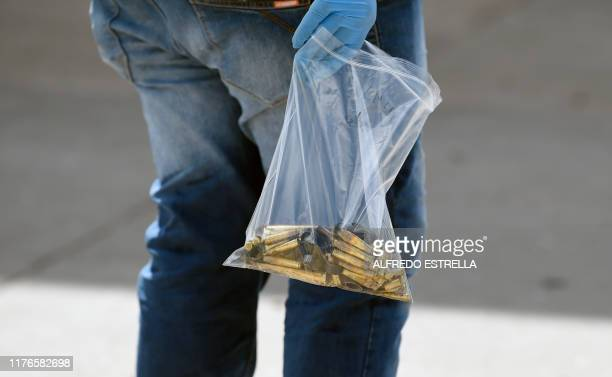 A forensic service employee collects bullet casings after heavily armed gunmen waged an allout battle against Mexican security forces in Culiacan...