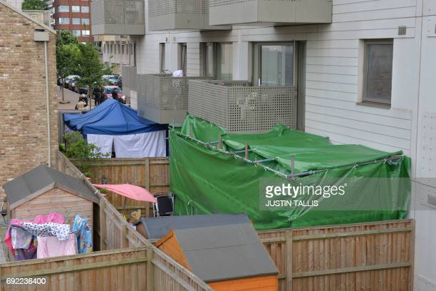 Forensic tents are set up in the gardens of two flats on Kings Road in Barking east London on June 4 as police continue their investigations...