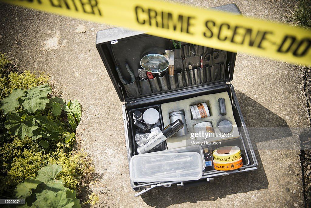 Forensic toolkit at crime scene with police tape : Stock Photo