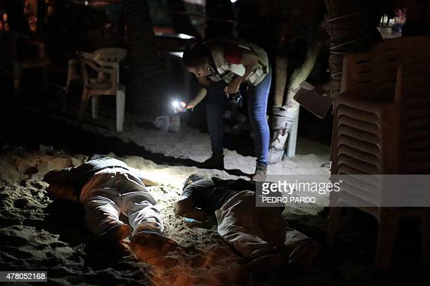 A forensic worker examines the bodies of two men executed at Papagayo beach in the tourist city of Acapulco Guerrero state on June 21 2015 Guerrero...