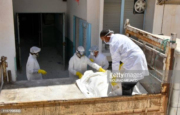 Forensic workers load into a truck the bodies of African migrants who were recovered on the Tunisian coast and will be buried at a communal cemetery...