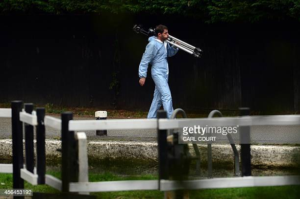 A forensics officer carries a tripod at the scene where a body was found during the search for missing schoolgirl Alice Gross in west London on...