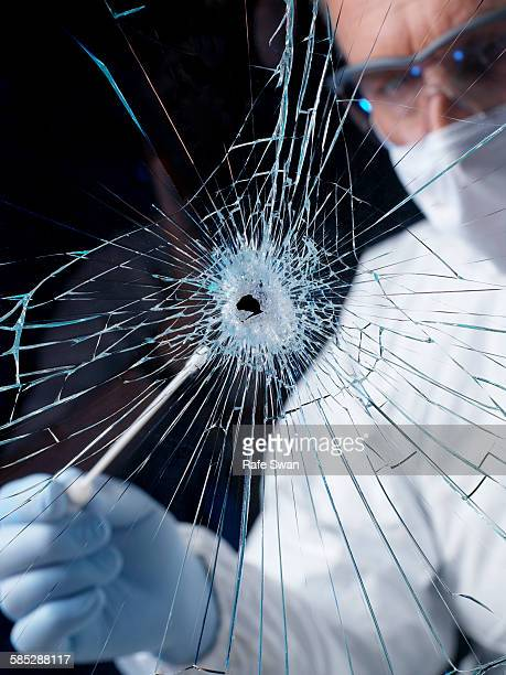 Forensics officer using swab to collect evidence from broken window