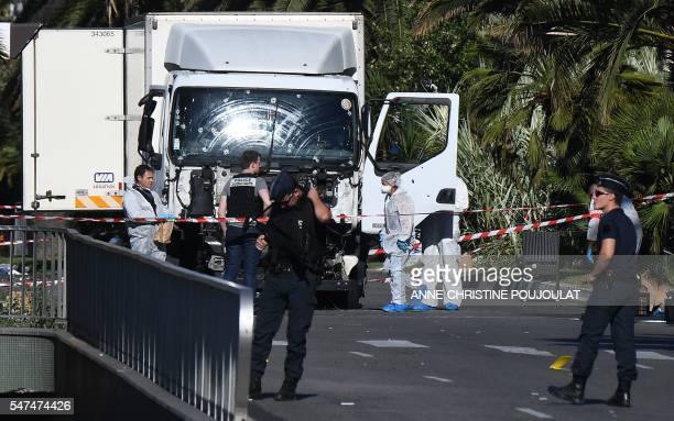 TOPSHOT Forensics officers and policemen look for evidences in a truck on the Promenade des Anglais seafront in the French Riviera town of Nice on...