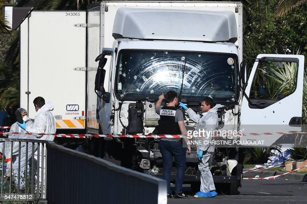 Forensics officers and policemen look for evidences near a truck on the Promenade des Anglais seafront in the French Riviera town of Nice on July 15...