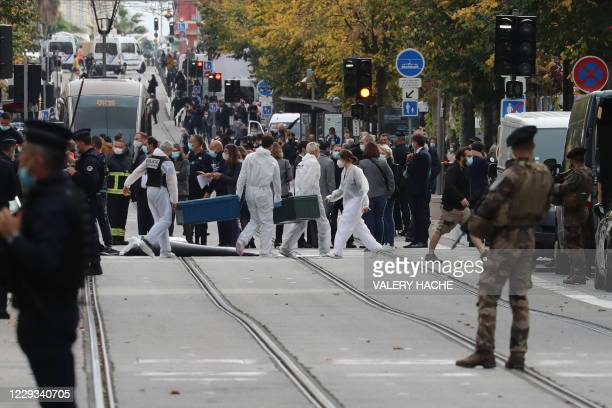 Forensics officers deploy stretchers at the site of a knife attack as French soldiers stand guard the street in Nice on October 29, 2020. - France's...