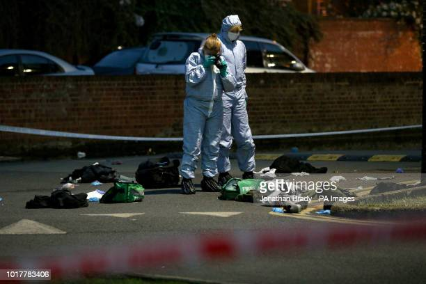 Forensics officers inspect the area outside Landor House Camberwell London after four people were taken to hospital with stab wounds Five males have...