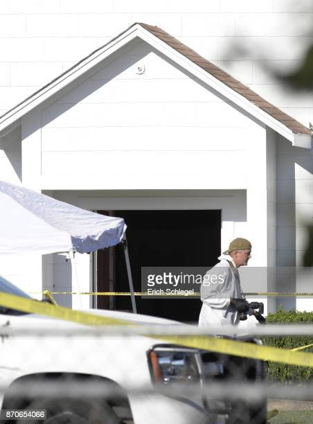 A forensics official passes by the entrance to the First Baptist Church following a shooting on November 5 2017 in Sutherland Springs Texas At least...