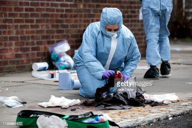Forensics teams work at the scene of a stabbing in Edmonton on March 31 2019 in London England Four people have been stabbed in a spate of knife...
