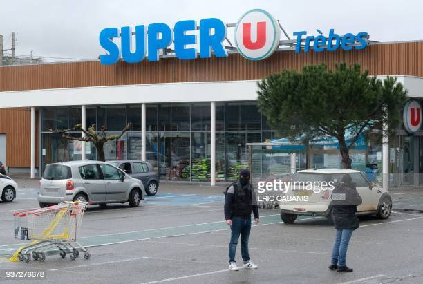 TOPSHOT Forensics work in front of the Super U supermarket in Trebes southwestern France on March 24 2018 where a man took hostages in a string of...