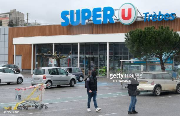Forensics work in front of the Super U supermarket in Trebes southwestern France on March 24 2018 where a man took hostages in a string of attacks...