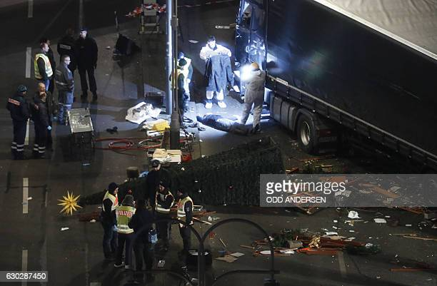 A foresnic police officer take a photo of a body on December 20 2016 at the scene where a truck crashed into a Christmas market near the...