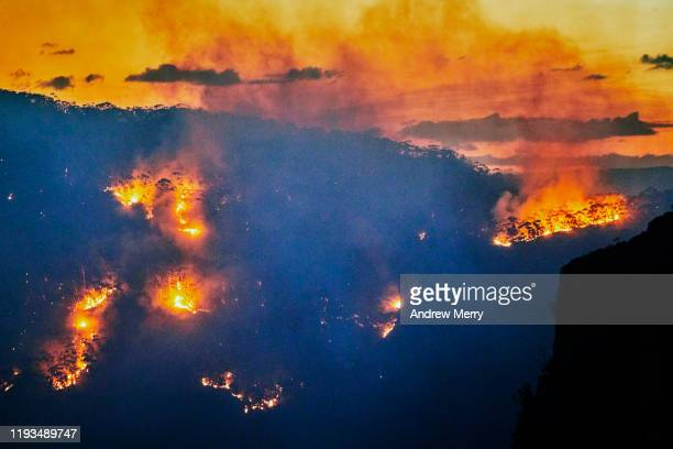 forest fire, bushfire with flames and smoke in valley at dusk, blue mountains, australia - australia fire stock pictures, royalty-free photos & images