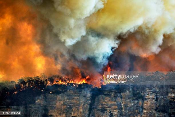forest fire, bushfire with flames and thick smoke clouds on the edge of rocky cliff in blue mountains, australia - meteo estremo foto e immagini stock