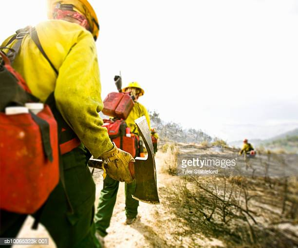 Forest firefighters walking with pickaxes, rear view