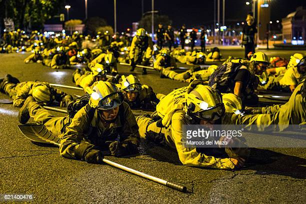 Forest firefighters wearing their working clothes lay down on the flor demanding better working conditions during a protest in Madrid Forest...
