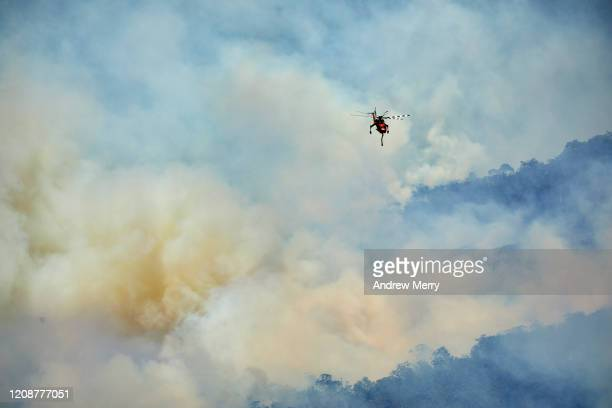 forest fires with firefighting helicopter aircraft in smoke filled valley, australia - helicopter stock pictures, royalty-free photos & images