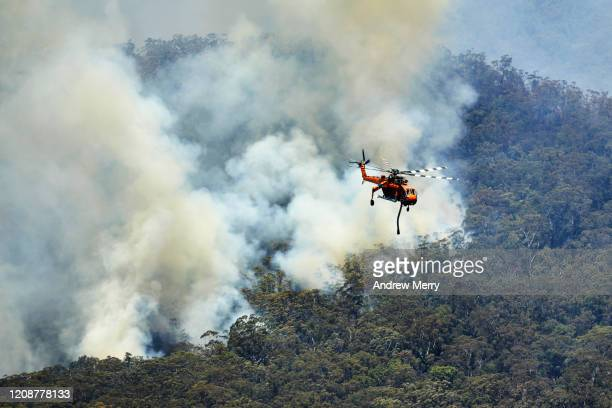 forest fires with firefighting helicopter aircraft water bombing bushfires in valley of eucalyptus trees, australia - australia bushfire stock pictures, royalty-free photos & images