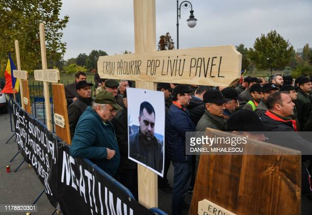 """Forest guards stand next to wooden crosses bearing the names of their killed colleagues, among them Liviu Pop , and erected in tribute of the """"forest..."""