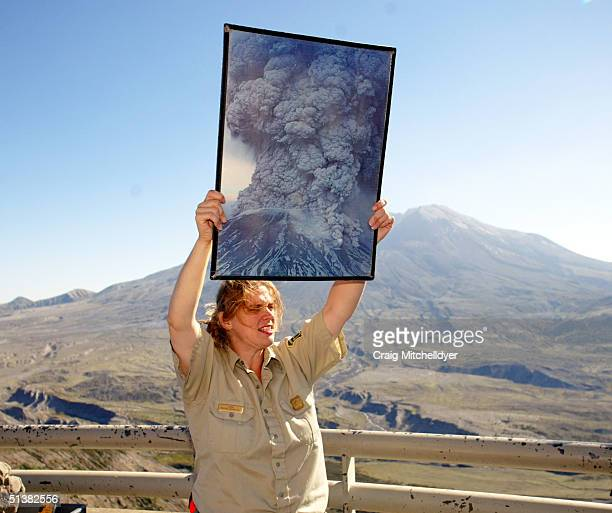 Forest service employee Anna White holds up a photo of the orignal eruption in 1980 while talking to visitors at Mount St. Helens from the Johnston...