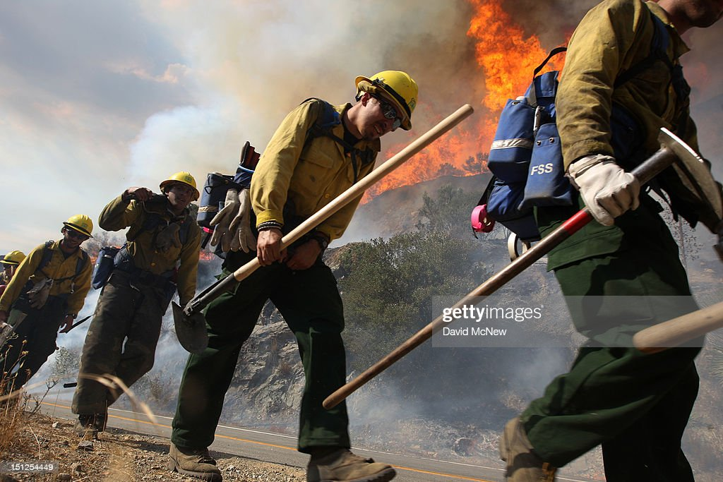 U.S. Forest Service firefighters walk near flames at the Williams fire in the Angeles National Forest on September 4, 2012 north of Glendora, California. The fire began late September 2, putting an early end to Labor Day weekend camping and hiking for vacationers, who were evacuated from the area as it spread to more than 4,000 acres in size. Officials project that it will take at least another week to establish a containment line around the fire which is burning in rugged and difficult to reach backcountry.