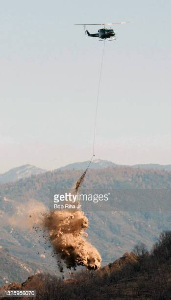 Forest Service helicopter makes a drop of rice straw on the hillsides recently ravaged by wild land fires to protect erosion in the San Bernardino...